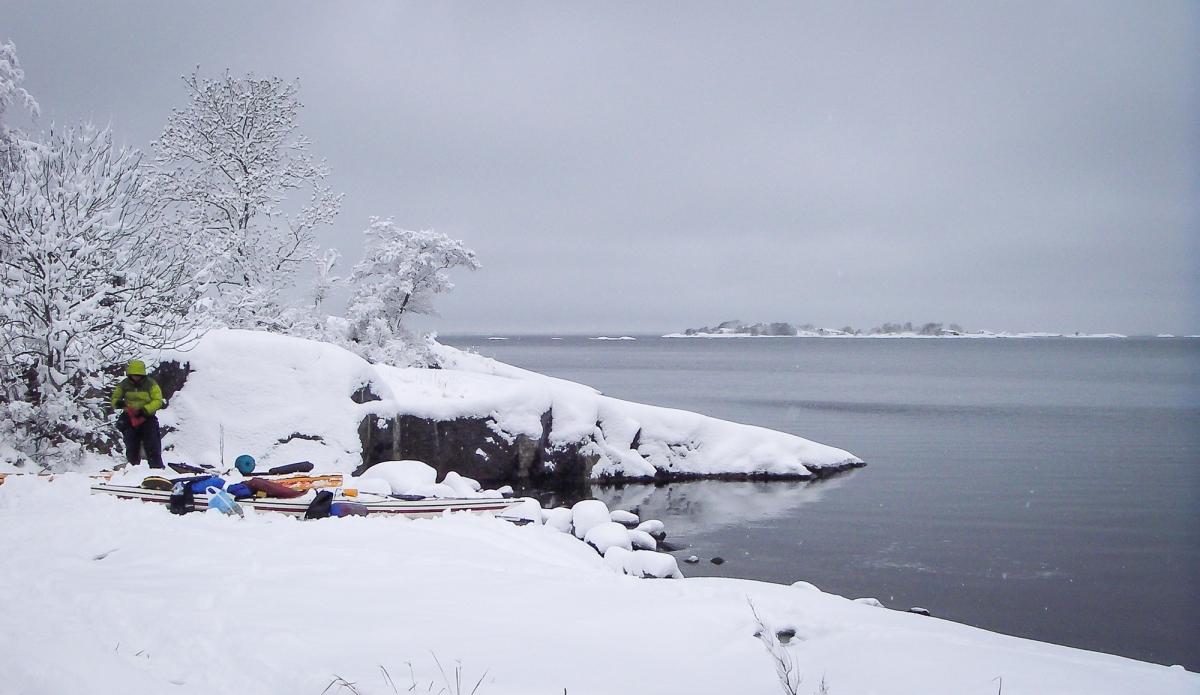 Paddlare packar kajak på översnöade klippor. Norrpada, Stockholms skärgård.