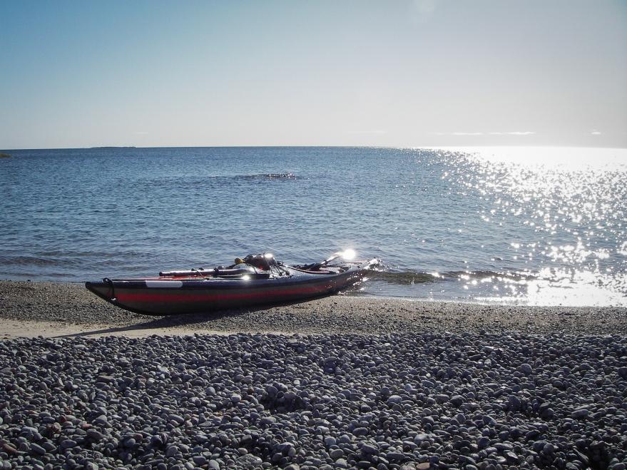 Kajak i strandkanten på stenstrand. Blå himmel och glittrig horisont i bakgrunden.
