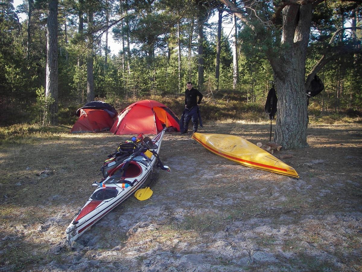 Kajakpaddlare står vid kajaker och tält på en strand vid skogskanten.