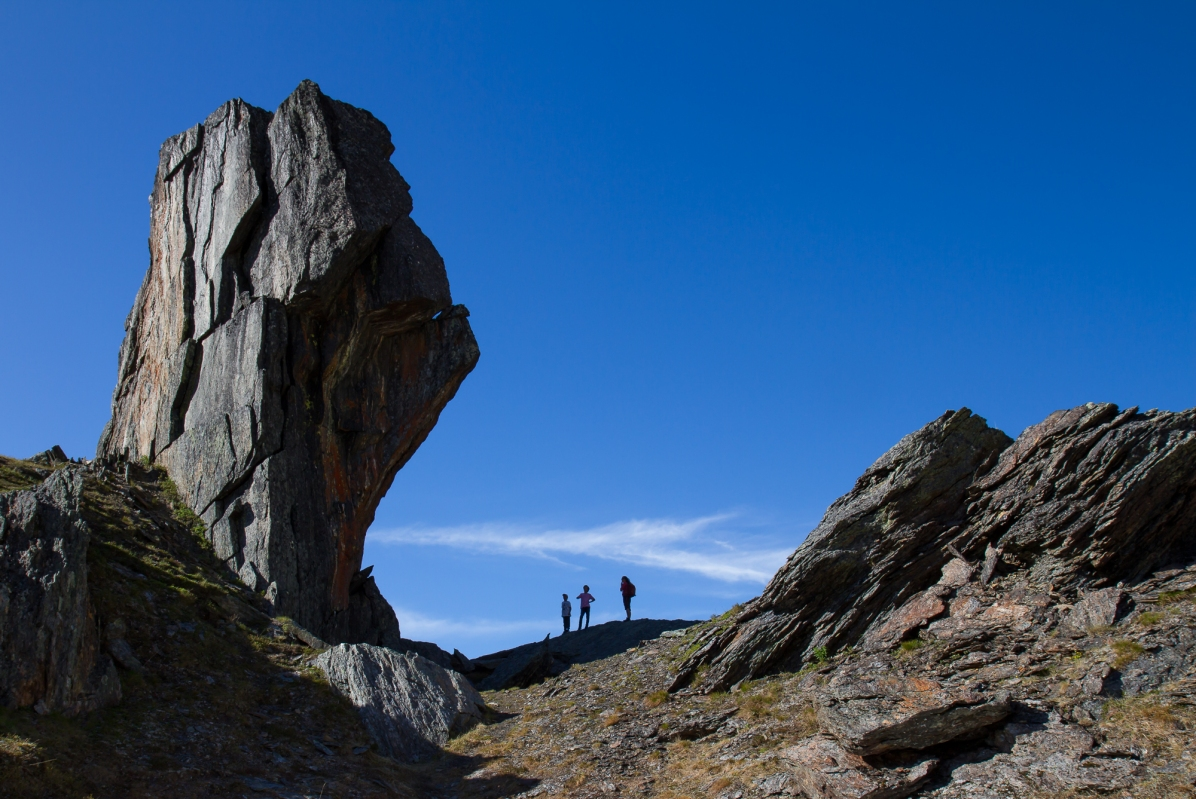 Silhouettes of hikers tells the scale of giant boulder in Kärkevagge.