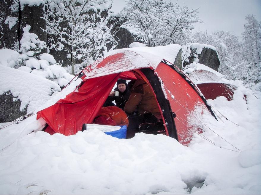 Två personer dricker morgonkaffe i översnöat tält på Norrpada, Stockholms skärgård.