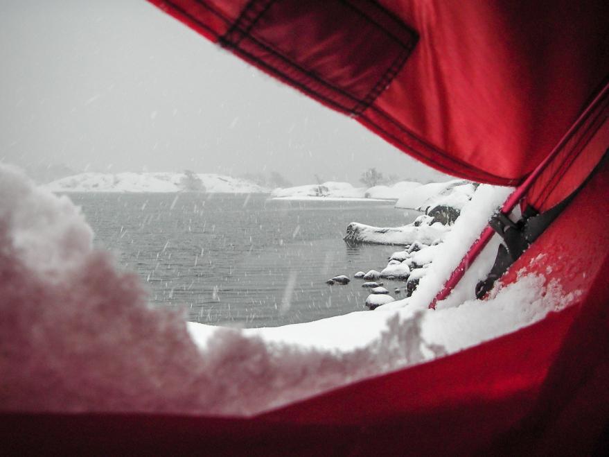 Norrpada i Stockholms skärgård i snöigt vinterväder, sett inifrån ett översnöat Hilleberg Staika- tält.