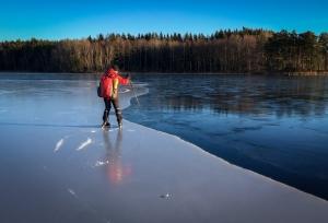 Långfärdsskridskoåkare känner sig fram längs kanten mot tunnare is.