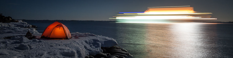 Rött tält på iskant i Stockholms skärgård på natten med ett förbipasserande kryssningsfartyg