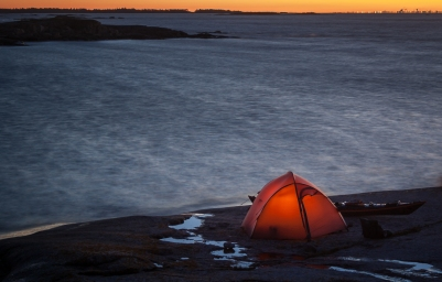 Skymning över kajakpaddlare som tältar på klippa alldeles intill vattnet i Stockholms skärgård