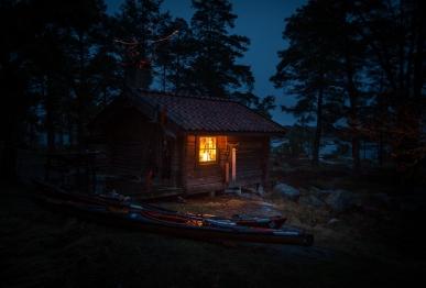 Två kajaker ligger i mörkret utanför en stuga i Stockholms skärgård