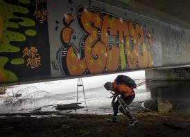 Långfärdsskridskoåkare går under en graffitimålad vägbro