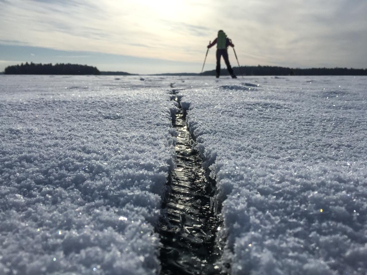 Långfärdsskridskoåkare passerar en spricka i isen på Björkfjärden