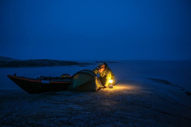 A man is preparing a divvy bag next to a sea kayak on a cliff close to the water