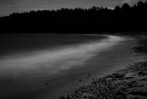 Vågor bryter mot strand i månljus