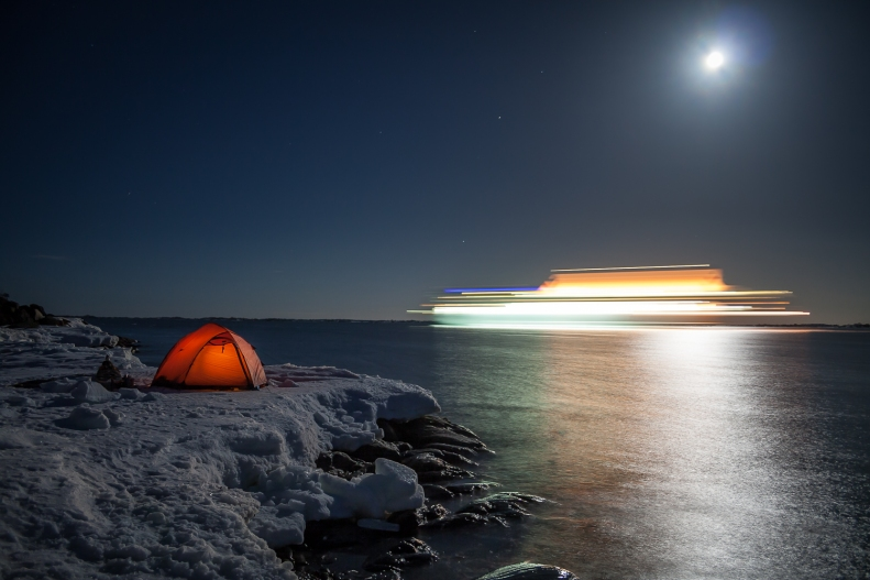 A sea kayakers tent on the ice by the sea in the moonlight with a cruise ship passing by