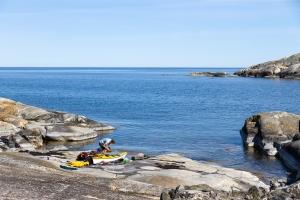 Kajakpaddlare tar lunch på klipporna i Söderarm, Stockholms skärgård