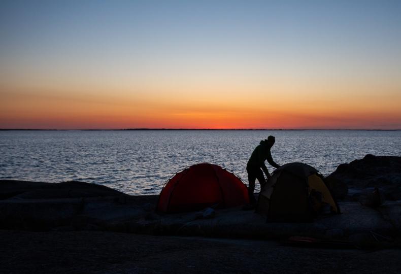 En person reser ett tält i solnedgången på Norrpada, Stockholms skärgård