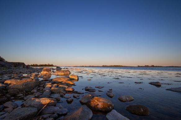 Kvällssol över stenar på stranden på Inre Håkanskär