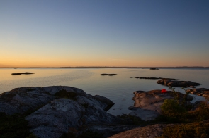 Solnedgång över kajak och tält i Kallskärs skärgård, Stockholms skärgard