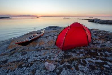 Solnedgång över kajak och tält i Kallskärs skärgård, Stockholms skärgård