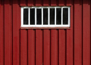 Ett vitt spröjsat fönster på en faluröd träpanelsvägg