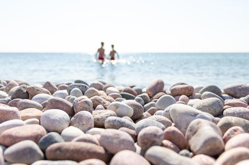 Två personer badar i havet vid en vacker stenstrand på Gotska Sandön