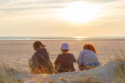 Tre personer sitter och njuter av solnedgången över Bredsandsudde, Gotska Sandön