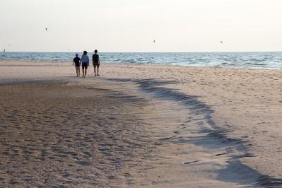 Tre personer promenerar på sandstranden Bredsandsudde, Gotska Sandön