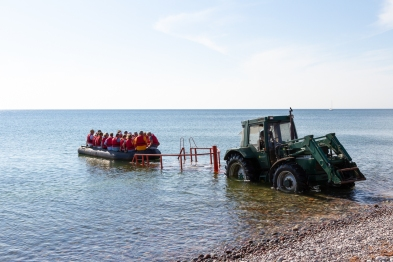 En gummibåt med passagerare blir sjösatt med hjälp av traktor, Gotska Sandön