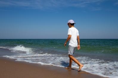 En kille promenerar längs strandkanten på en av Gotska Sandöns underbara stränder
