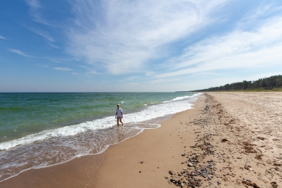 En kille promenerar längs en sandstranden Las Palmas på Gotska Sandön