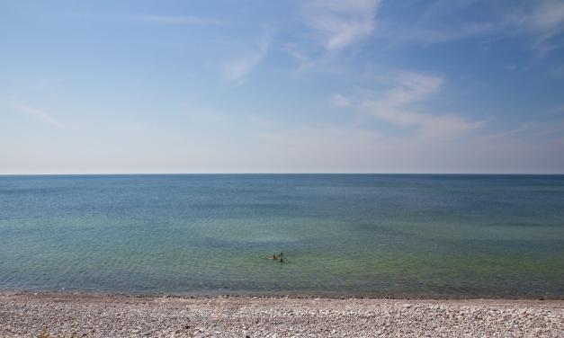 Tre personer badar i havet vid stenstranden Varvsbukten på Gotska Sandön