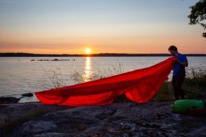 En person förbereder en tarp för sonplats i solnedgången
