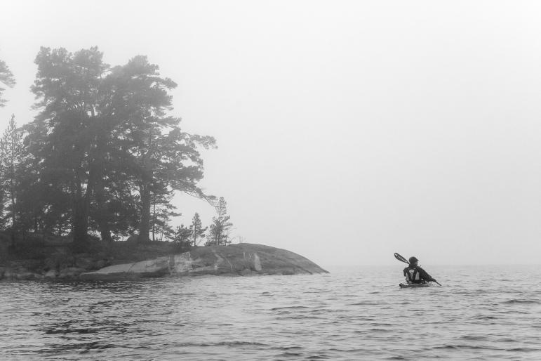 Kajakpaddlare i dimma i Stockholms skärgård
