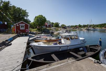 Fritidsbåtar ligger vid gästbryggan i Rödlöga hamn, Stockholms skärgård