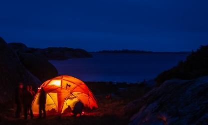 Kajakpaddlare i mörkret utanför ett upplyst tält på Bullerön, Stockholms skärgård