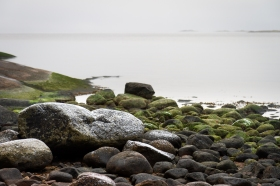 Pudersnö över stenar på stranden, Sörmlands skärgård