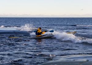 Kajakpaddlare paddlar genom vågor vid Tärnskär, Stockholms skärgård