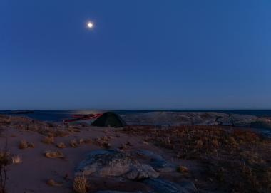 Månsken över tält och kajaker på Tärnskär, Stockholms skärgård