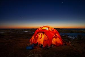 Ett upplyst tält på Tärnskär med det sista färgstarka ljuset vid horisonten i bakgrunden