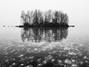 Enslig ö speglar sig i blank kärnis med infrusna snöfläckar