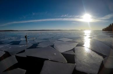 Långfärdsskridskoåkare letar sig fram bland isflaken på Singöfjärden, Stockholms norra skärgård