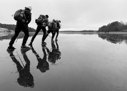 Långfärdsskridskoåkare på rulle speglas i blank kärnis