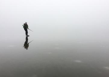 Långfärdsskridskoåkare i dimma speglas i blank kärnis