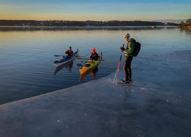 Långfärdsskridskoåkare möter kajakpaddlare i gryningen längs iskanten på Stora Värtan
