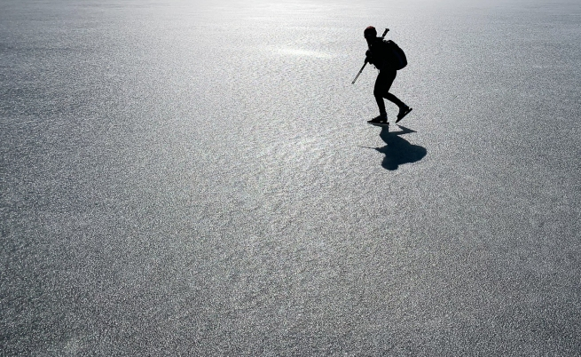 Långfärdskridskoåkare i motljus på sjön Båven, Sörmland