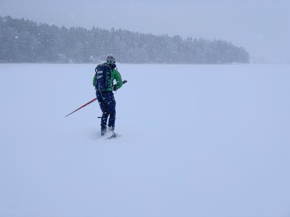 Långfärdsskridskoåkare plöjer fram i ymnigt snöfall över Stora Värtan