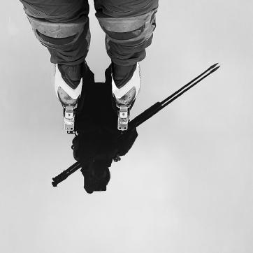 Långfärdsskridskoåkare speglar sig i blank kärnis