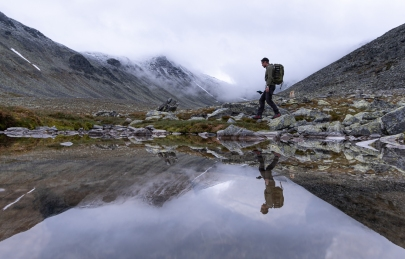 Reflektion i vattnet av en person som vandrar i Rondane nationalpark, Norge