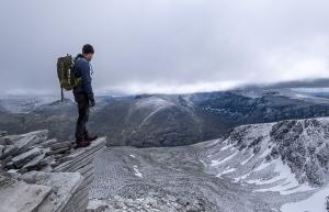 En person blickar ut över vidsträckt fjälldal i Rondane nationalpark, Norge