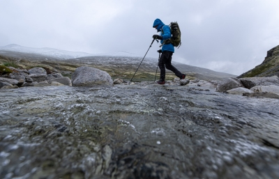 En person vandrar över en bäck i Rondane nationalpark, Norge