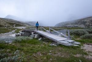 En person vandrar över en bro i Rondane nationalpark, Norge