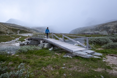 En person vandrar över en bro i Rondane nationalpark, Norge