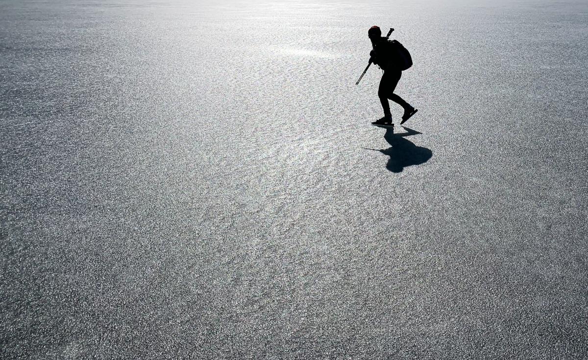 Silhuette av långfärdsskridskoåkare på sjön Båven i Sörmland